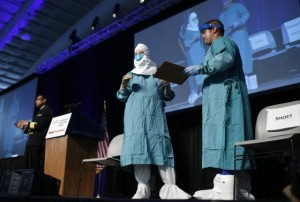 Smith and Christensen of the of the CDC's Domestic Infection Control Team for Ebola demonstrate putting on personal protective equipment during an Ebola educational session for healthcare workers in New York